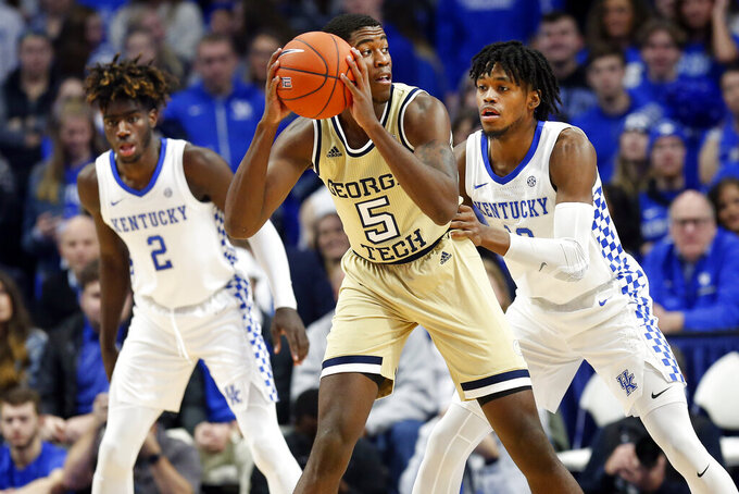 Georgia Tech's Moses Wright, center, looks for an opening on Kentucky's Keion Brooks Jr., right, and Kahlil Whitney, left, during the first half of an NCAA college basketball game in Lexington, Ky., Saturday, Dec. 14, 2019. (AP Photo/James Crisp)