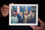 In this Friday, June 19, 2020 photo, Journalist and author Benjamin Pogrund holds a photo showing him, center, next to Nelson Mandela, at his house in Jerusalem, Friday, June 19, 2020. Pogrund spent decades battling apartheid as a journalist in South Africa. Since moving to Israel two decades ago, he has passionately defended the country against charges that it too is an apartheid state.(AP Photo/Oded Balilty)