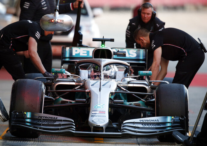 FILE - In this file photo dated Thursday, Feb. 21, 2019, Mechanics prepare Mercedes driver Valtteri Bottas of Finland car during a Formula One pre-season testing session at the Barcelona Catalunya racetrack in Montmelo, outside Barcelona, Spain. Previewing the upcoming 2019 season, for Bottas, even though he didn't win a single race in 2018, the Finnish driver still believes he can be a genuine challenger for the title this season, even though that will mean challenging his Mercedes teammate Lewis Hamilton. (AP Photo/Joan Monfort, FILE)