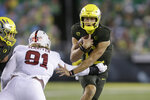 Oregon's Tyler Shough, right, evades Stanford's Thomas Schaffer, center, on a quarterback keeper during the first quarter of an NCAA college football game Saturday, Nov. 7, 2020, in Eugene, Ore. (AP Photo/Chris Pietsch)