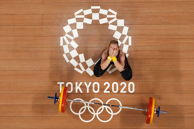 Sabine Beate Kusterer of Germany gestures after an unsuccessful lift during the women's 59kg weightlifting event, at the 2020 Summer Olympics, Tuesday, July 27, 2021, in Tokyo, Japan. (AP Photo/Luca Bruno)