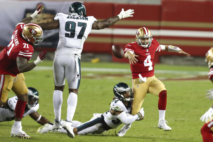 San Francisco 49ers quarterback Nick Mullens (4) fumbles the ball as he runs from Philadelphia Eagles cornerback Cre'von LeBlanc, bottom, which was recovered by defensive tackle Malik Jackson (97), during the second half of an NFL football game in Santa Clara, Calif., Sunday, Oct. 4, 2020. (AP Photo/Jed Jacobsohn)
