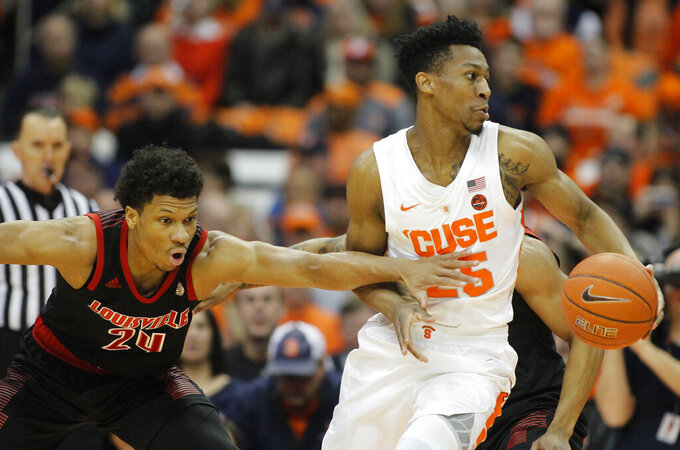 Syracuse's Tyus Battle, right, dribbles past Louisville's Dwayne Sutton, left, during the first half of an NCAA college basketball game in Syracuse, N.Y., Wednesday, Feb. 20, 2019. (AP Photo/Nick Lisi)