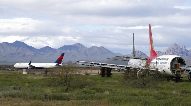 A recently landed Delta Air Lines plane  is towed past two stripped passenger planes at Pinal Airpark Wednesday, March 18, 2020, in Red Rock, Ariz., as many passenger planes are being kept at the facility as airlines cut back on service due to the coronavirus. (AP Photo/Ross D. Franklin)