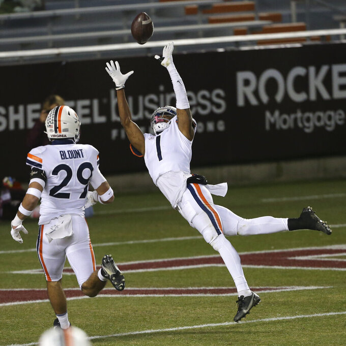 Virginia's Nick Grant, right, attempts to intercept a pass from Virginia Tech quarterback Braxton Burmeister during the first half of an NCAA college football game Saturday, Dec. 12, 2020, in Blacksburg, Va. (Matt Gentry/The Roanoke Times via AP, Pool)