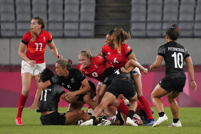 New Zealand and Britain players battling for the ball look up toward an official, in their women's rugby sevens match at the 2020 Summer Olympics, Thursday, July 29, 2021 in Tokyo, Japan. (AP Photo/Shuji Kajiyama)