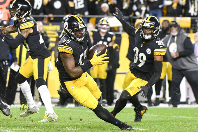 Pittsburgh Steelers inside linebacker Devin Bush (55) advances a fumble by Seattle Seahawks quarterback Geno Smith (7) in overtime of an NFL football game, Sunday, Oct. 17, 2021, in Pittsburgh. The Steelers won 23-20 in overtime. (AP Photo/Don Wright)
