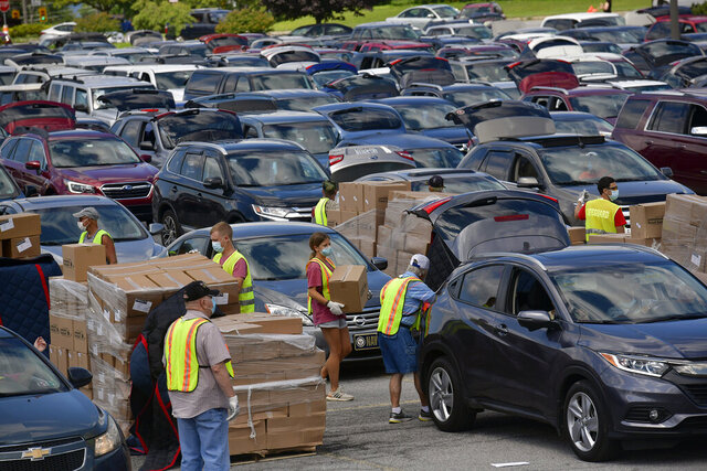 Volunteers load up vehicles at the Johnstown Galleria in Johnstown, Pa. for the fourth Greater Pittsburgh Community Food Bank drive-up distribution event on Wednesday, August 5, 2020. (Todd Berkey/The Tribune-Democrat via AP)