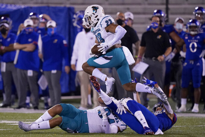 Coastal Carolina cornerback Derick Bush (23) leaps over players after intercepting a pass during the first half of an NCAA college football game in Lawrence, Kan., Saturday, Sept. 12, 2020. (AP Photo/Orlin Wagner)
