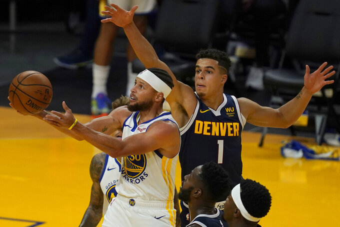 FILE - In this Dec. 12, 2020, file photo, Golden State Warriors guard Stephen Curry, left, shoots against Denver Nuggets forward Michael Porter Jr. (1) during the first half of a preseason NBA basketball game in San Francisco. The 32-year-old Curry has already said he wants to remain with the Warriors for the rest of his career and perhaps play until he's 40, but for now staying healthy in the present is a top priority. (AP Photo/Jeff Chiu, File)