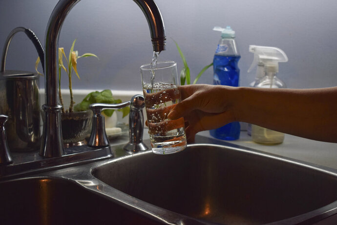 In this July 21, 2019 photo, Florabela Cunha fills a glass of water from her kitchen faucet in Prince Rupert, British Columbia, Canada. In previous summers she used to make iced tea for her family using water from her tap, but has since stopped citing concerns about the water quality. Hundreds of thousands of Canadians from coast to coast have been unwittingly exposed to levels of lead in their drinking water. (Mackenzie Lad/Institute for Investigative Journalism/Concordia University via AP)