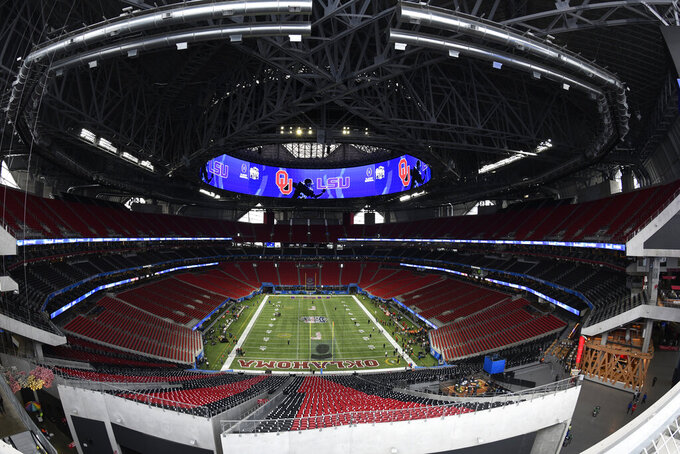 FILE - In this Dec. 28, 2019, file photo, The Mercedes-Benz stadium is shown prior to the Peach Bowl NCAA college football playoff game between LSU and Oklahoma in Atlanta. The Final Four teams would've been in Atlanta, getting in their final practices for Saturday's semifinal games. The $1.5 billion stadium, a retractable-roof wonder normally used for football and soccer, would have undergone a hasty reconfiguration to essentially construct a new lower deck stretching all the way to courtside. Those seats would've been filled with 80,000 fans. (AP Photo/Danny Karnik, File)