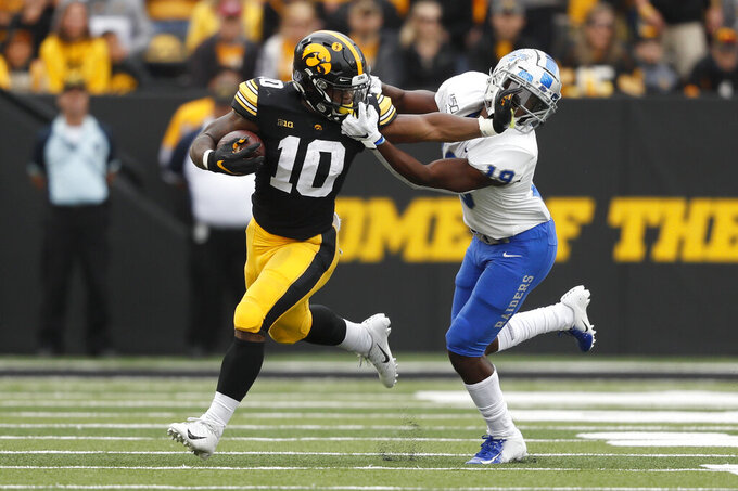 Iowa running back Mekhi Sargent (10) tries to break a tackle by Middle Tennessee cornerback Teldrick Ross, right, during the first half of an NCAA college football game, Saturday, Sept. 28, 2019, in Iowa City, Iowa. (AP Photo/Charlie Neibergall)