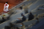 Spectators are blurred by a glass separation wall as Serbia's Novak Djokovic uses his towel in the quarterfinal match of the French Open tennis tournament against Spain's Pablo Carreno Busta at the Roland Garros stadium in Paris, France, Wednesday, Oct. 7, 2020. (AP Photo/Alessandra Tarantino)