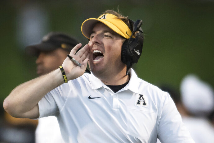 FILE - In this Sept. 28, 2019, file photo, then-Appalachian State head coach Eli Drinkwitz shouts in the second quarter of an NCAA football game against Coastal Carolina, in Boone, N.C. The debut season for Missouri coach Eli Drinkwitz got much more challenging when the Southeastern Conference adjusted its schedules this summer. Missouri's original cross-division opponents in its SEC schedule were Arkansas and Mississippi State, which both finished below .500 last season. But when the SEC switched to a format in which each team will play 10 conference games, Missouri discovered it also would be hosting Alabama and visiting defending national champion LSU.(Allison Lee Isley/The Winston-Salem Journal via AP, File)