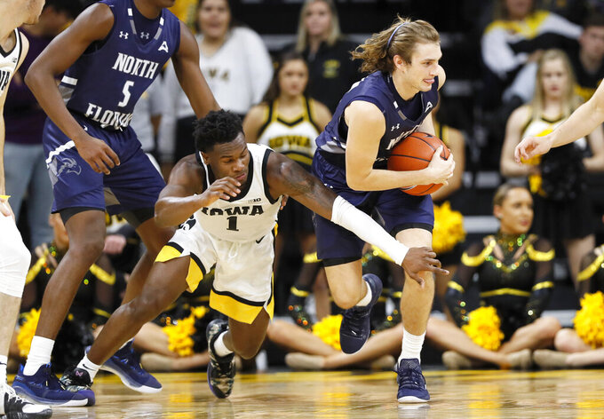 Iowa guard Joe Toussaint (1) tries to steal the ball from North Florida guard Ryan Burkhardt during the second half of an NCAA college basketball game, Thursday, Nov. 21, 2019, in Iowa City, Iowa. (AP Photo/Charlie Neibergall)