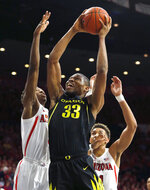 Oregon forward Francis Okoro (33) drives between Arizona guard Dylan Smith, left, and Chase Jeter (4) in the first half of an NCAA college basketball game, Thursday, Jan. 17, 2019, in Tucson, Ariz. (AP Photo/Rick Scuteri)