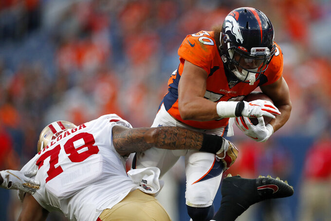 Denver Broncos running back Phillip Lindsay (30) is stopped by San Francisco 49ers defensive end Jeremiah Valoaga (78) during an NFL preseason football game, Monday, Aug. 19, 2019, in Denver. (AP Photo/David Zalubowski)
