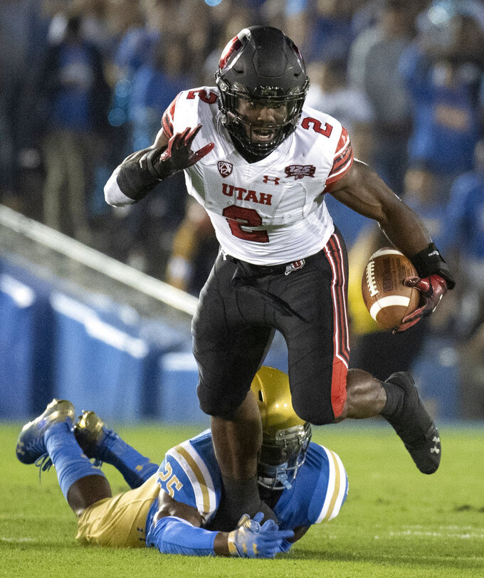 Utah running back Zack Moss, top, sprints over a tackle by UCLA linebacker Tyree Thompson during the first half of an NCAA college football game Friday, Oct. 26, 2018, in Pasadena, Calif. (AP Photo/Kyusung Gong)