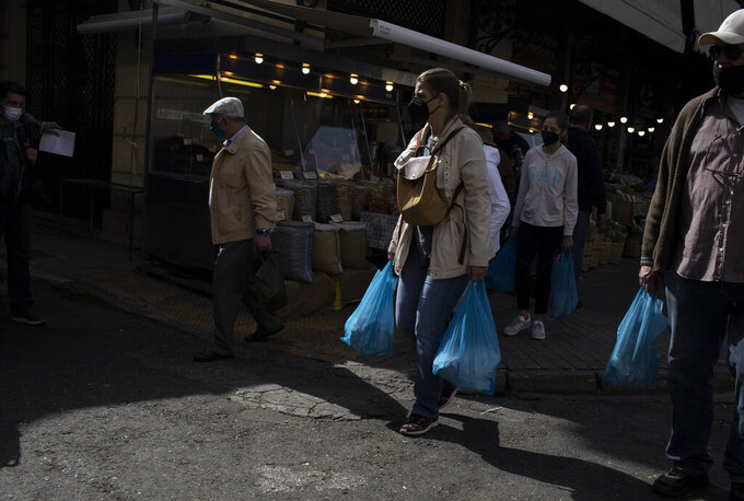 People wearing protective face masks carry bags with meat outside the meat market of Athens during the Orthodox Holy Week, Thursday, April 29, 2021. (AP Photo/Petros Giannakouris)