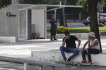 Skateboarders talk at Las Americas Square while a police officer stands guard outside a government-run Chivo machine, from the state-owned Banco Hipotecario, that will soon exchange cash for Bitcoin cryptocurrency, in San Salvador, El Salvador, Saturday, Sept. 4, 2021. Starting Tuesday, Sept. 7, all businesses will have to accept payments in Bitcoin, except those lacking the technology to do so. (AP Photo/Salvador Melendez)