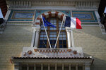 FILE - In this Thursday, Feb. 11, 2021 file photo, European and French flags fly at the entrance of the French National School of Administration, (ENA), in Paris. French President Emmanuel Macron on Thursday, April 8, 2021 detailed plans to do away with an elite academic institution that's a key symbol of the country's power establishment, replacing it with a more egalitarian version. Macron was addressing hundreds of civil servants by video conference about planned reforms in the top ranks of the civil service, including putting an end to the Ecole Nationale d'Administration, widely known as ENA. (AP Photo/Francois Mori, File)