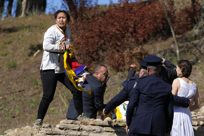 Police officers detain protesters displaying a Tibetan flag and a banner disrupting the lighting of the Olympic flame at Ancient Olympia site, birthplace of the ancient Olympics in southwestern Greece, Monday, Oct. 18, 2021. The flame will be transported by torch relay to Beijing, China, which will host the Feb. 4-20, 2022 Winter Olympics. (AP Photo/Thanassis Stavrakis)