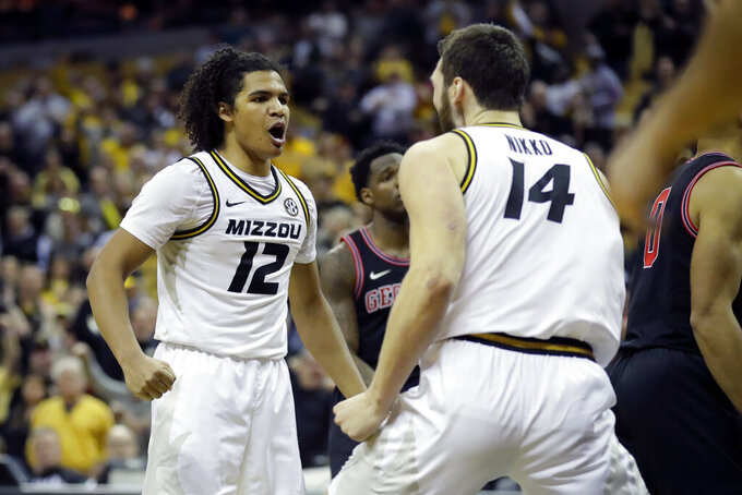Missouri's Dru Smith (12) and Reed Nikko (14) celebrate late in the second half of the team's NCAA college basketball game against Georgia on Tuesday, Jan. 28, 2020, in Columbia, Mo. Missouri won 72-69. (AP Photo/Jeff Roberson)