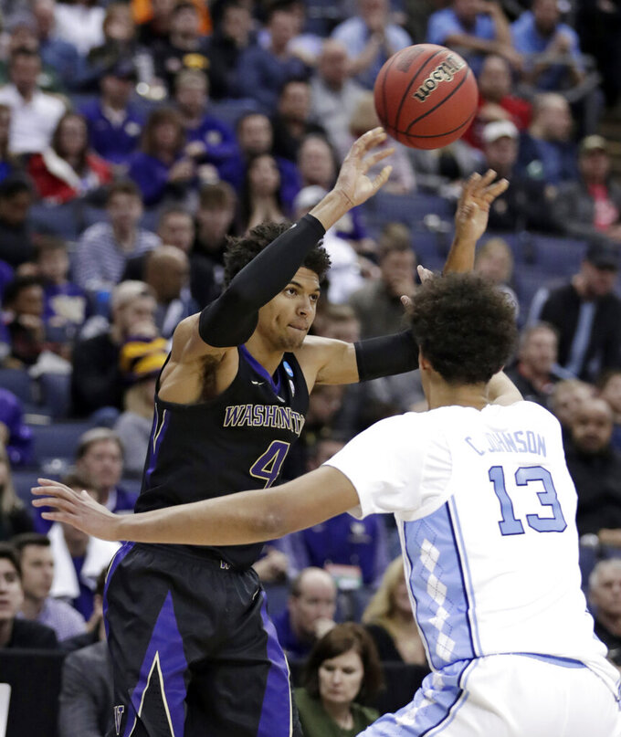 Washington's Matisse Thybulle (4) passes over North Carolina's Cameron Johnson (13) in the second half during a second round men's college basketball game in the NCAA Tournament in Columbus, Ohio, Sunday, March 24, 2019. North Carolina won 81-59.(AP Photo/Tony Dejak)