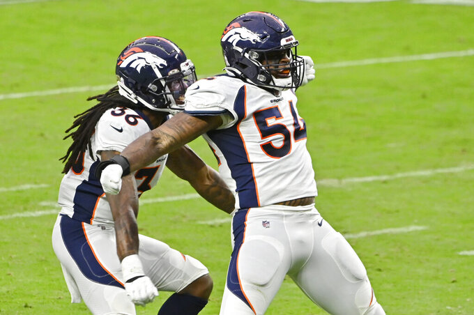 Denver Broncos safety Trey Marshall (36) and linebacker Josh Watson (54) celebrate after a play against the Las Vegas Raiders during the first half of an NFL football game, Sunday, Nov. 15, 2020, in Las Vegas. (AP Photo/David Becker)
