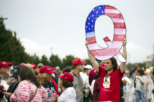 FILE - In this Aug. 2, 2018, file photo, a protesters holds a Q sign waits in line with others to enter a campaign rally with President Donald Trump in Wilkes-Barre, Pa.   Facebook and Twitter promised to stop encouraging the growth of the baseless conspiracy theory QAnon, which fashions President Donald Trump as a secret warrior against a supposed child-trafficking ring run by celebrities and government officials. But the social media companies haven't succeeded at even that limited goal, a review by The Associated Press found.  (AP Photo/Matt Rourke, File)