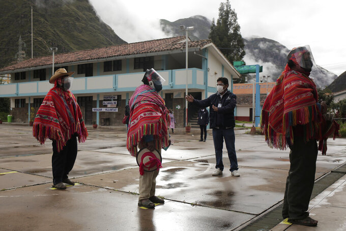 An electoral official instructs voters to keep social distance to prevent the spread of the new coronavirus during general elections in Ollantaytambo, Peru, Sunday, April 11, 2021. (AP Photo/Sharon Castellanos)
