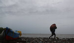 A fisherman walks with his belongings on the shores of the Arabian Sea in Mumbai, India, Wednesday, June 3, 2020. A storm in the Arabian Sea off India's west coast intensified into a severe cyclone on Wednesday, gathering speed as it barreled toward India's financial capital of Mumbai. Nisarga was forecast to drop heavy rains and winds gusting up to 120 kilometers (75 miles) per hour when it makes landfall Wednesday afternoon as a category 4 cyclone near the coastal city of Alibagh, about 98 kilometers (60 miles) south of Mumbai, India's Meteorological Department said. (AP Photo/Rafiq Maqbool)