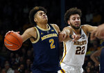Michigan's Jordan Poole, left, drives as Minnesota's Gabe Kalscheur defends in the second half of an NCAA college basketball game Thursday, Feb. 21, 2019, in Minneapolis. (AP Photo/Jim Mone)