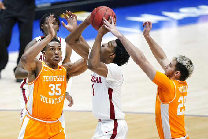 Alabama's Herbert Jones (1) is defended by Tennessee's Yves Pons (35) and Santiago Vescovi (25) in the first half of an NCAA college basketball game in the Southeastern Conference Tournament Saturday, March 13, 2021, in Nashville, Tenn. (AP Photo/Mark Humphrey)