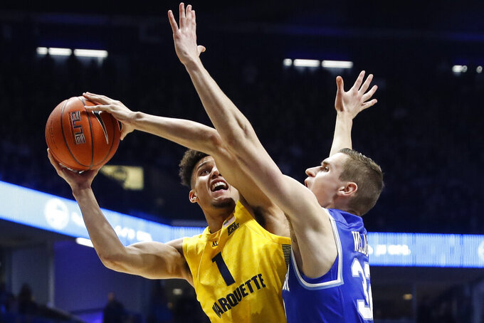Marquette's Brendan Bailey (1) shoots against Xavier's Ryan Welage, right, in the second half of an NCAA college basketball game, Saturday, Jan. 26, 2019, in Cincinnati. (AP Photo/John Minchillo)