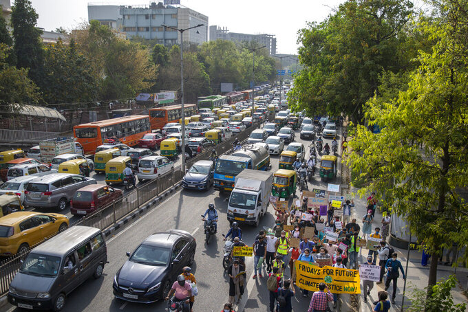 Student activists carry posters and shout slogans as they participate in a protest march against climate change in New Delhi, India, Friday, March 19, 2021. India has ambitions to expand use of electric vehicles to wean itself from polluting fossil fuels, but EVs are still a rarity on its congested highways. A lack of charging stations and poor quality batteries are discouraging drivers from switching over. (AP Photo/Altaf Qadri)