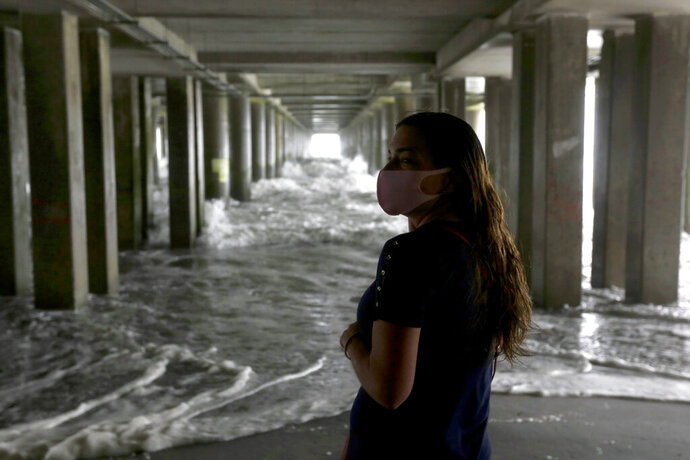 Melissa Allphin, a tourist from Detroit, watches waves crash under a pier as the Atlantic Ocean churns Tuesday, Aug. 4, 2020, in Atlantic City, N.J. Tropical Storm Isaias spawned tornadoes and dumped rain during an inland march up the U.S. East Coast, including New Jersey, on Tuesday after making landfall as a hurricane along the North Carolina coast. (AP Photo/Jacqueline Larma)