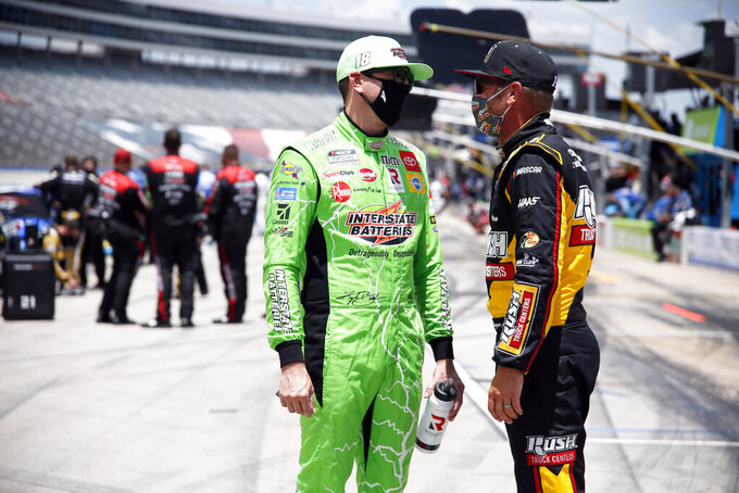Kyle Busch, left, and Clint Bowyer, right, talk on pit road prior to a NASCAR Cup Series auto race at Texas Motor Speedway in Fort Worth, Texas, Sunday, July 19, 2020. (AP Photo/Ray Carlin)