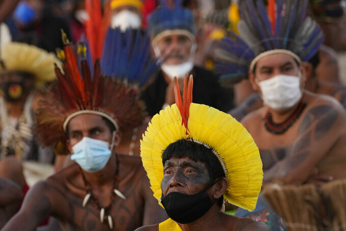 Indigenous people watch a Supreme Court session on a TV screen, that is expected to issue a ruling that will have far-reaching implications for tribal land rights, outside the Supreme Court building, in Brasilia, Brazil, Wednesday, Aug. 25, 2021. (AP Photo/Eraldo Peres)