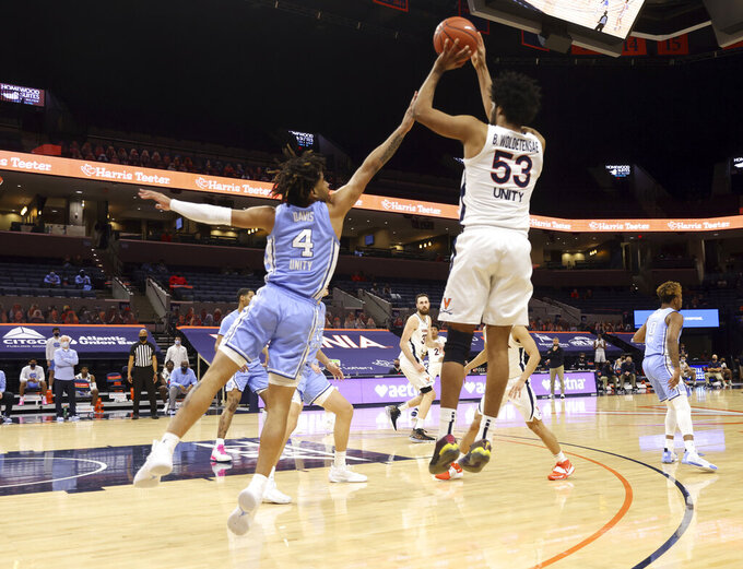 Virginia guard Tomas Woldetensae (53) shoots over North Carolina guard R.J. Davis (4) during an NCAA college basketball game Saturday, Feb. 13, 2021, in Charlottesville, Va. (Andrew Shurtleff/The Daily Progress via AP, Pool)