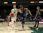 Miami forward Sam Waardenburg (21) drives against Notre Dame forward Juwan Durham (11) during the first half of an NCAA college basketball game, Wednesday, Feb. 6, 2019 in Coral Gables, Fla. (David Santiago/Miami Herald via AP)