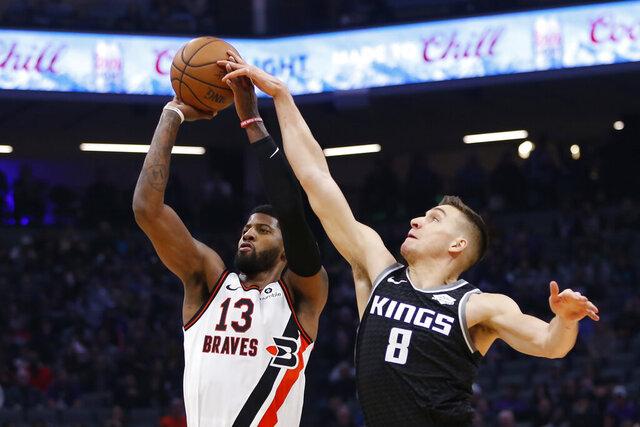 El escolta de los Kings de Sacramento Bogdan Bogdanovic bloquea el tiro del alero de los Clippers de Los Ángeles Paul George en la primera mitad del juego del martes 31 de diciembre de 2019, en Sacramento. (AP Foto/Rich Pedroncelli)