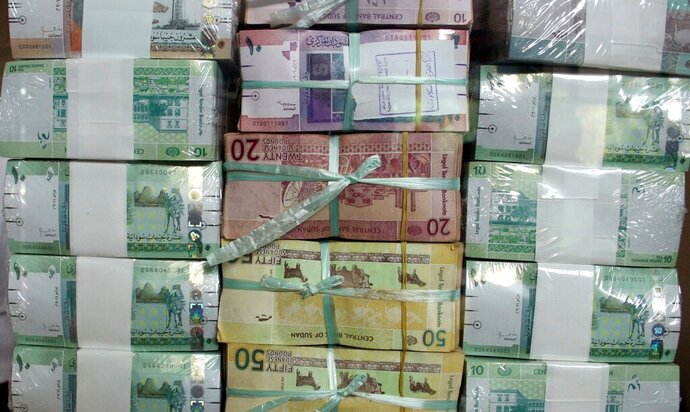 FILE - In this Sunday, July 24, 2011 file photo, Sudan's banknotes are displayed behind a window at the central bank in Khartoum, Sudan. Sudan's annual inflation has hit a new record peak as prices of bread and other staples keep surging, according to official figures released on Tuesday. (AP Photo/Abd Raouf, File)