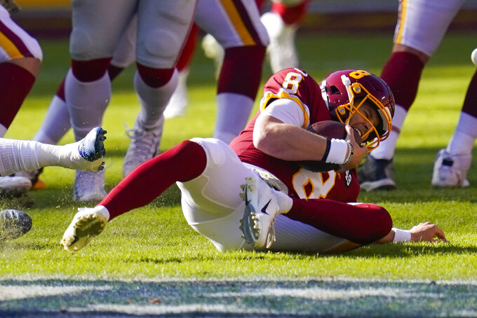 Washington Football Team quarterback Kyle Allen (8) reacting as he injures his leg in a play against New York Giants in the first half of an NFL football game, Sunday, Nov. 8, 2020, in Landover, Md. (AP Photo/Patrick Semansky)