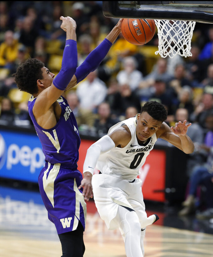 Washington guard Matisse Thybulle, left, dunks for a basket over Colorado guard Shane Gatling during the first half of an NCAA college basketball game Saturday, Jan. 12, 2019, in Boulder, Colo. (AP Photo/David Zalubowski)