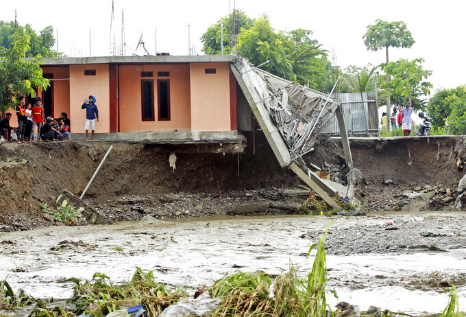 People inspect buildings damaged by a flood in Dili, East Timor, Monday, April 5, 2021. Multiple disasters caused by torrential rains in eastern Indonesia and neighboring East Timor have left dozens of people dead and missing and displaced thousands. (AP Photo/Kandhi Barnez)