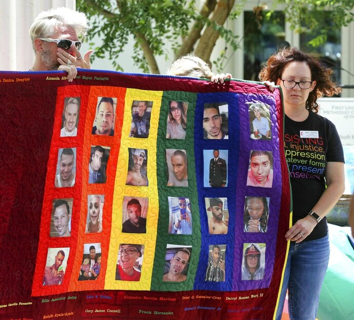 Douglas Barrett, left, and Rev. Shelly Denmark, with others, hold a memorial quilt during the tolling of the bells and reading of the names at First United Methodist Church in Orlando, Fla., Wednesday, June 12, 2019, on the 3rd anniversary of the Pulse nightclub massacre. (Joe Burbank/Orlando Sentinel via AP)