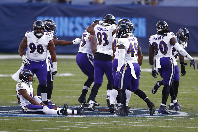 Baltimore Ravens players sit and stand on the Tennessee Titans' logo at the 50-yard line after Ravens cornerback Marcus Peters intercepted a pass against the Titans late in the fourth quarter of an NFL wild-card playoff football game Sunday, Jan. 10, 2021, in Nashville, Tenn. (AP Photo/Wade Payne)