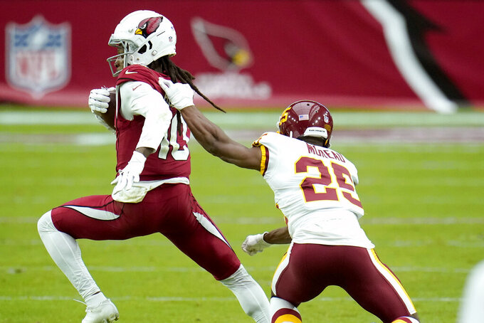 Washington Football Team cornerback Fabian Moreau (25) grabs Arizona Cardinals wide receiver DeAndre Hopkins (10) during the second half of an NFL football game, Sunday, Sept. 20, 2020, in Glendale, Ariz. (AP Photo/Ross D. Franklin)